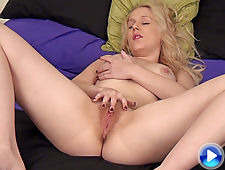 On her bed, Aston Wilde rubs her pussy and strips