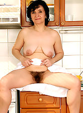 52 year old Sandra shows off her full bush and tits in her kitchen